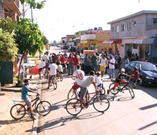 Foto de crianças em suas bicicletas e adultos com cartazes agrupados para iniciar uma manifestação na rua.