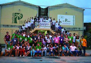 Foto da equipe de trabalho da cidade reunida em frente à sede do Banco Palmas
