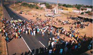 Cidadãos reunidos em via principal da cidade, organizados para realizar manifestação.