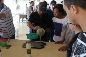 Foto mostra senhor despejando a mistura de cimento em forma de plástico junto a outras pessoas que participam do processo.