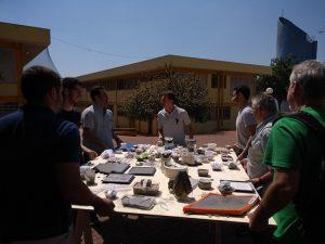 Foto de uma mesa de produção da oficina de moldagem. Há 7 pessoas no entorno e a mesa está na parte descoberta do CEU Heliópolis, com o prédio do CEU e o dia ensolarado ao fundo.