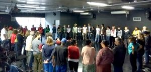 Foto mostra uma roda de mais de 40 pessoas em uma sala fechada durante a atividade de sensibilização.
