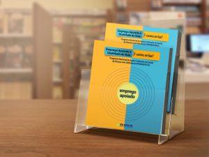 Foto do livro sobre a metodologia do Emprego Apoiado exposto em frente a outras prateleiras de livros.